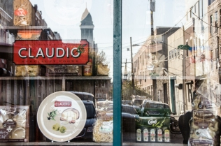 Claudio's, a staple in the market since the 1950s, displays imported items while reflecting both rehabbed and old facades on Montrose Street. Renters, owners, industrial, it's there. Rising above it all is the cupola of 124-year-olf St. Mary Magdalen de Pazzi church, the first Italian national parish in the U.S., closed for the last 15 years.